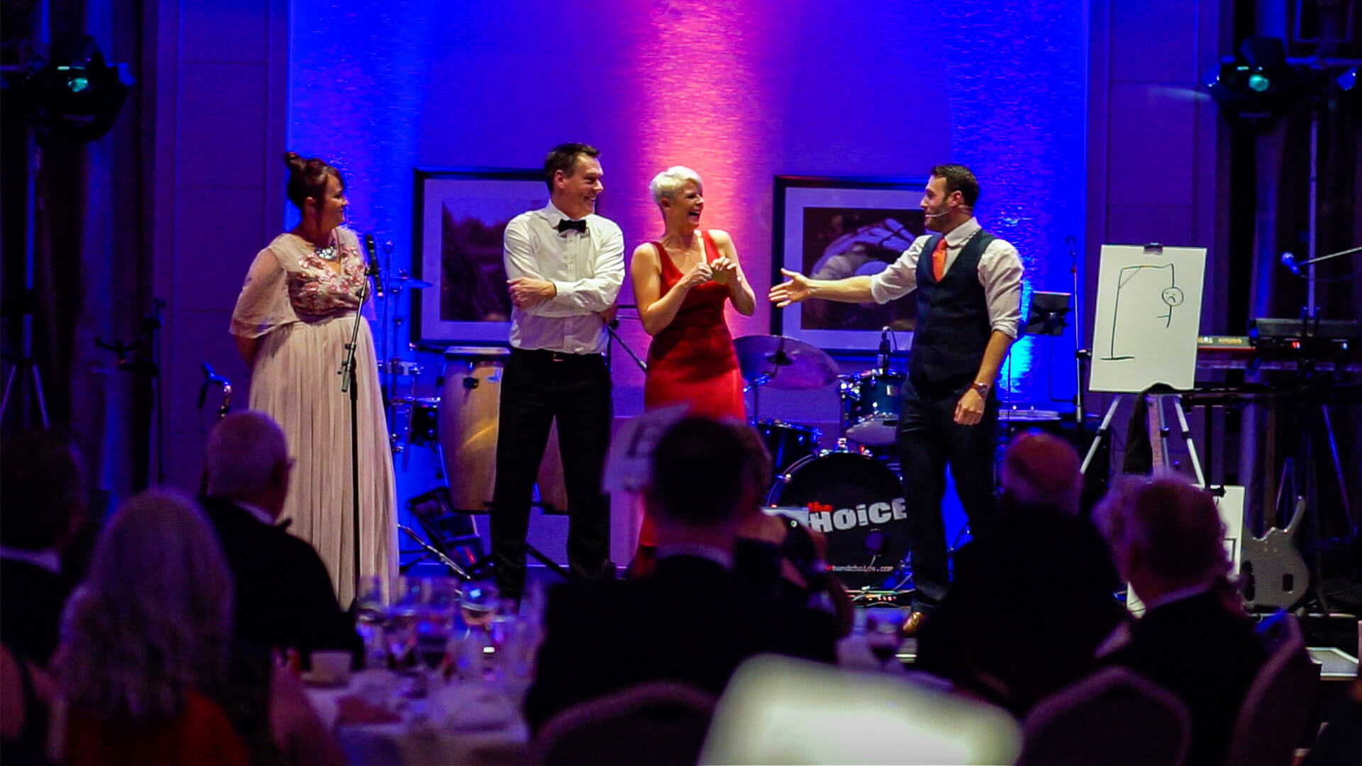 Corporate event entertainment Mind reader and hypnotist Aaron Calvert on stage with three amazed guests