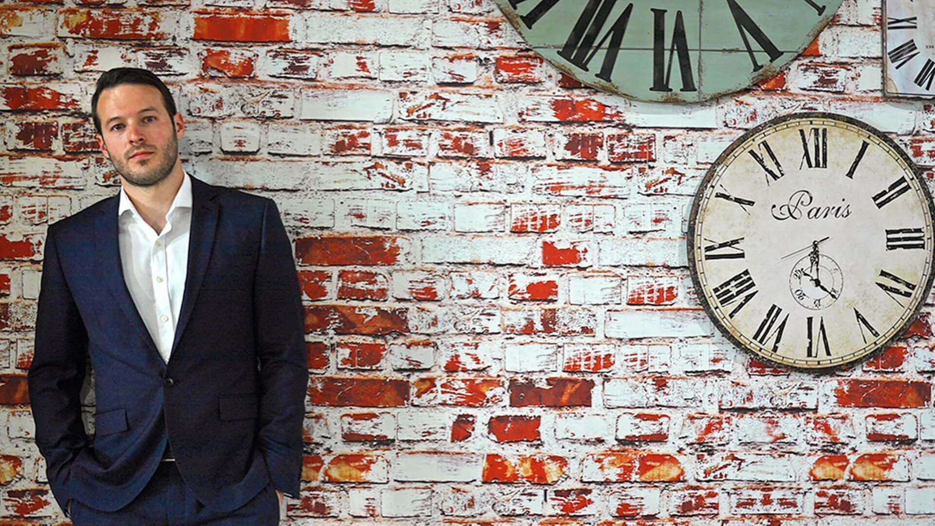 Aaron Calvert leaning against a brick wall with clocks ready for his edinburgh fringe magic show