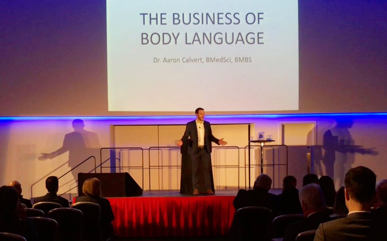 corporate training talk by speaker mind reader and hypnotist dr Aaron Calvert on stage delivering presentation