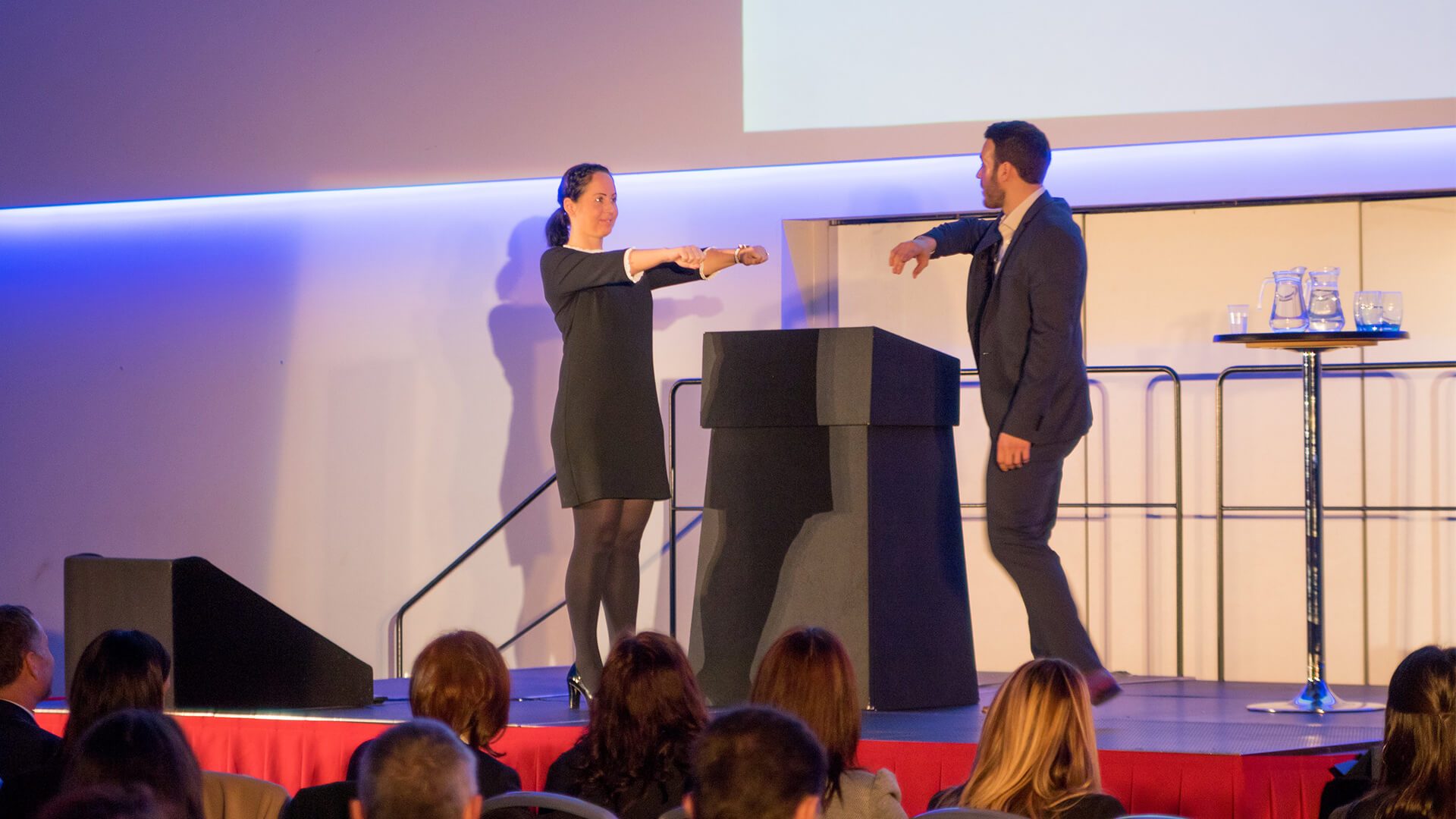 Aaron demonstrating the psychology of business on stage at Corporate event as Manchester magician