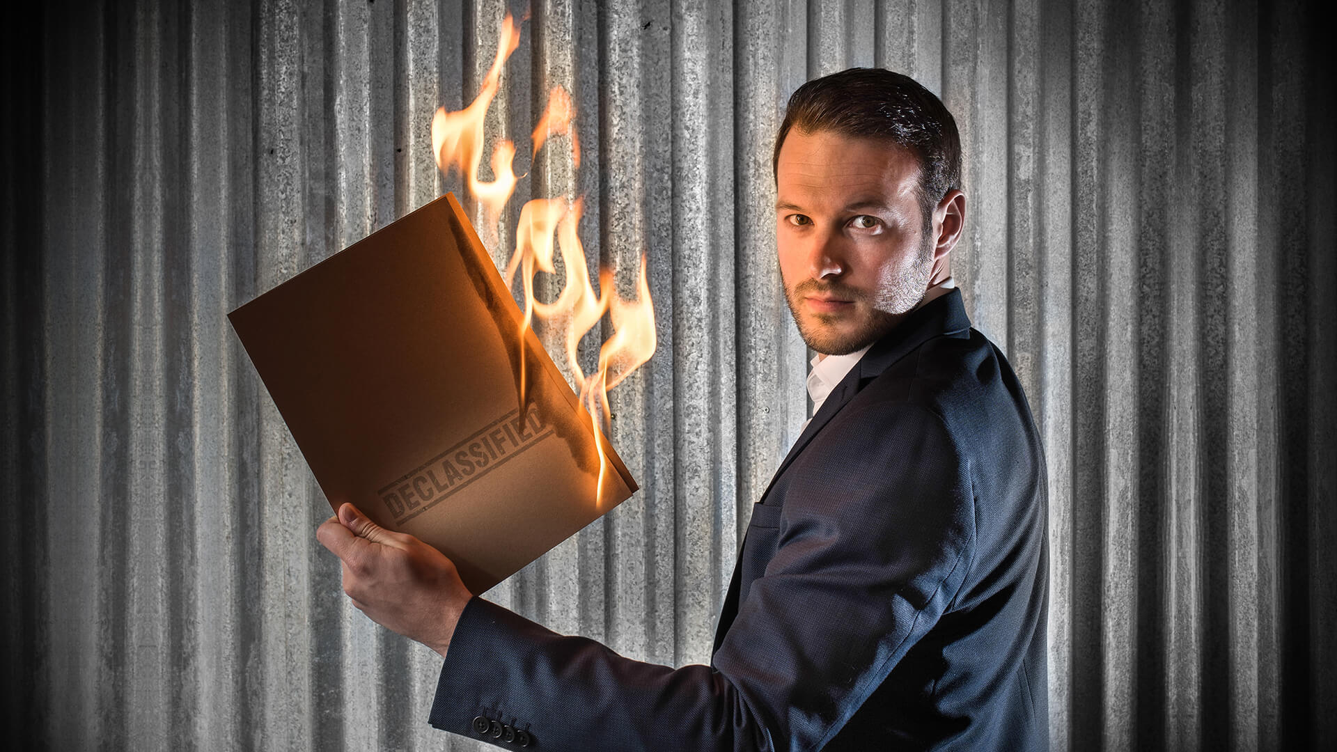 Aaron Calvert holding burning declassified file for edinburgh fringe magic show declassified at the gilded balloon
