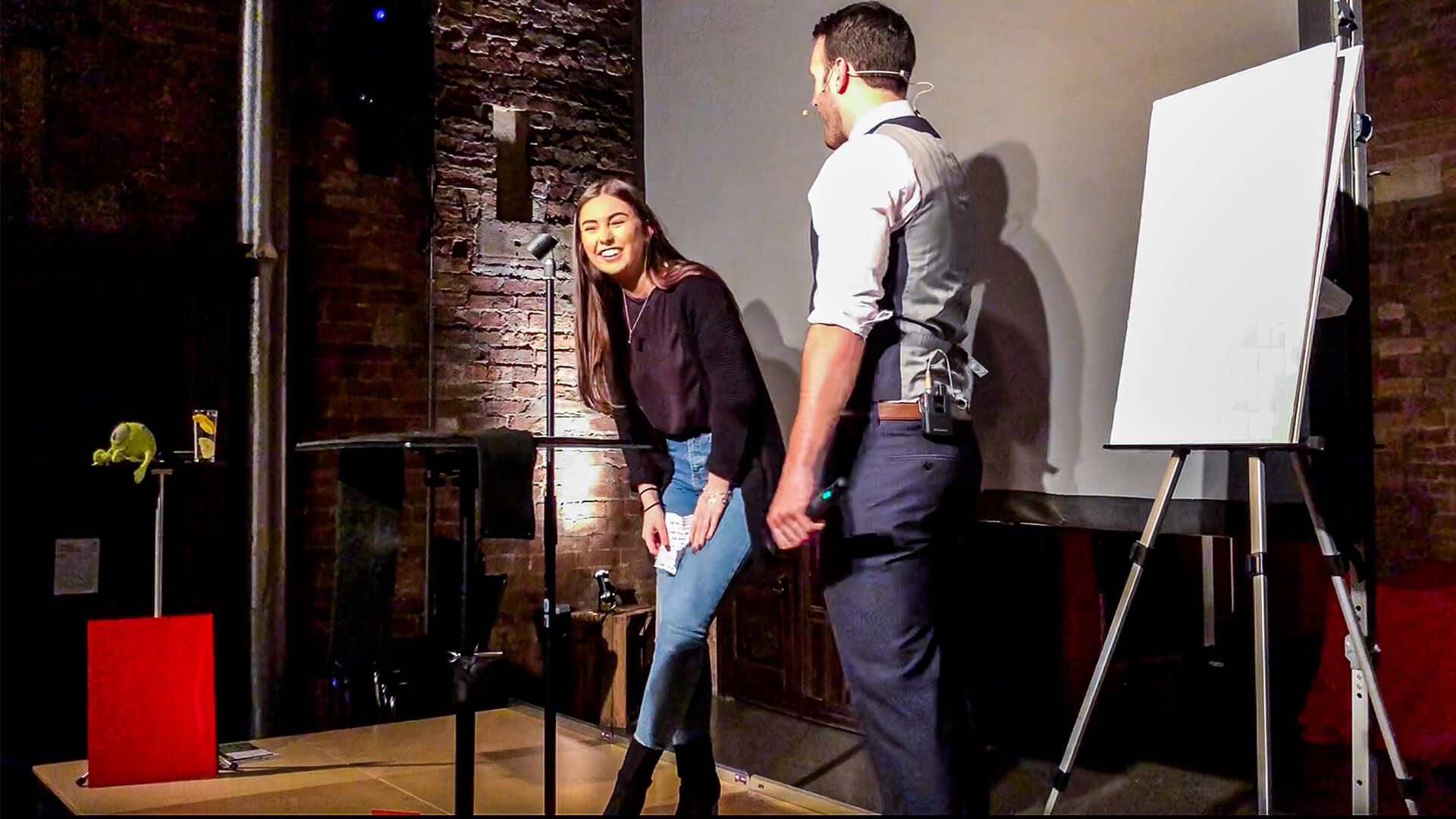 Corporate event entertainment Mind reader and hypnotist Aaron Calvert on stage with girl laughing at incredible show