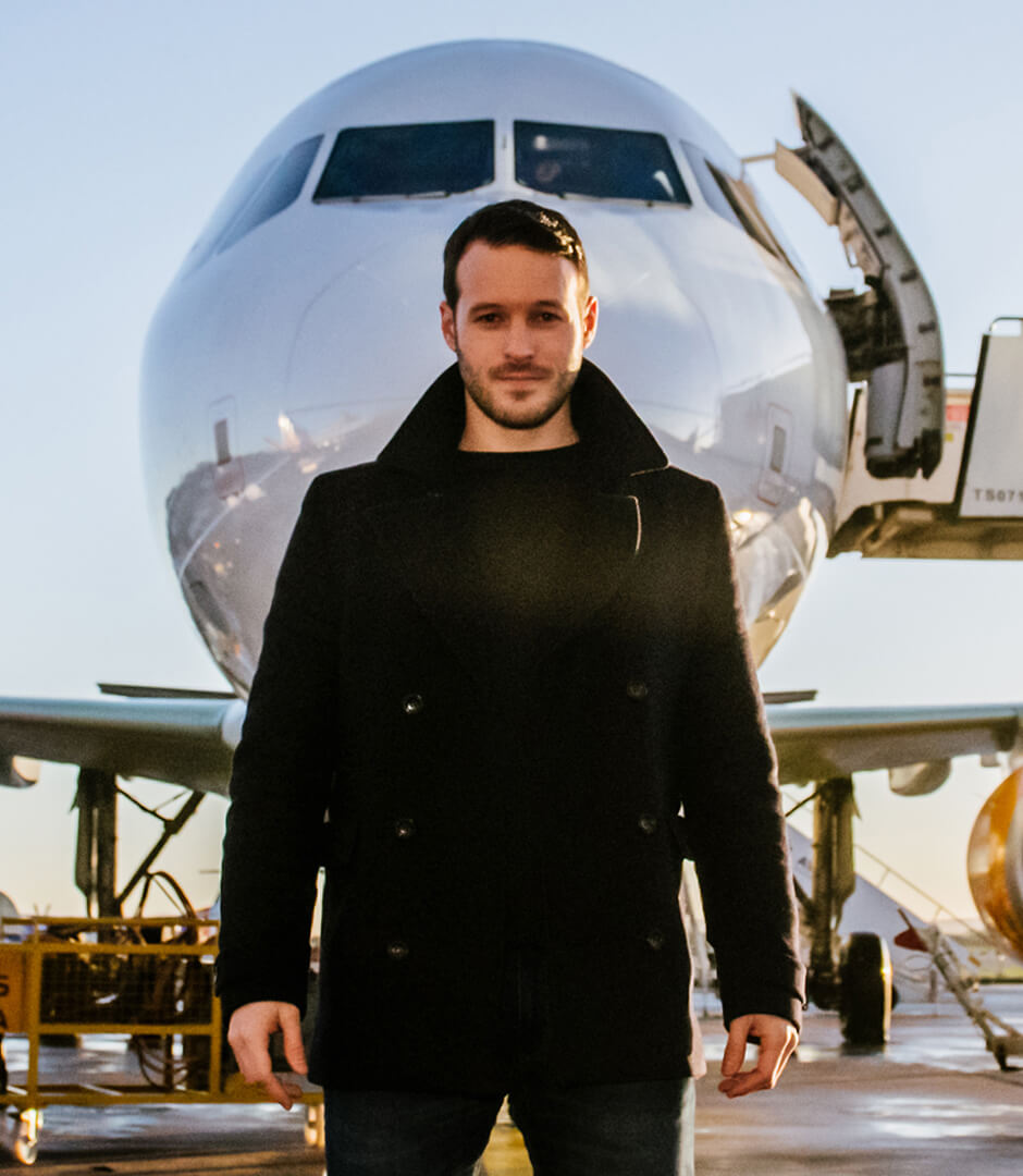Corporate event entertainment Mind reader and hypnotist Aaron Calvert in front of Thomas Cook Airlines plane for hypnosis experiment with first time fliers
